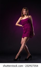 Beautiful sexy young woman in purple dress dancing on dark purple background in studio - series of photos