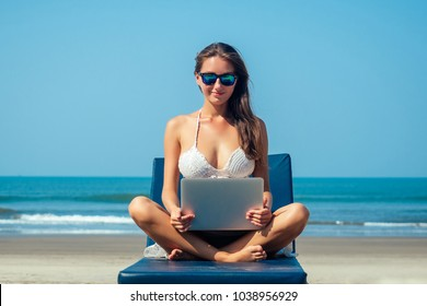 beautiful and sexy young woman sitting in lotus pose and medetiruet on a lounger with a laptop by the sea. woman freelancer doing yoga with a laptop in the resort