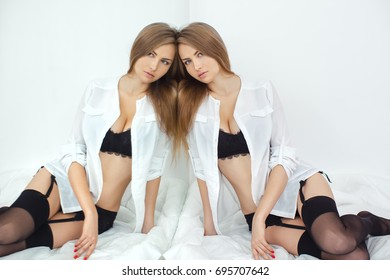 Beautiful sexy young woman in a white shirt and black lingerie with long blond hair looking at camera near the mirror against white background