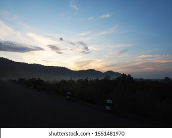 Beautiful shade light of sunrise. Landscape of sunrise. Sky, mountain, cloud, tree, kilometer stone and road in the dawn time. Sadness and alone concept.