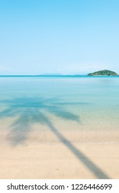 Beautiful shadow of palm tree on the blue sea in summer. Relaxation tropical seascape, green islands and light blue sky backgrounds. Sunshine day. Koh Mak Island, Trat, Thailand. Vacation time concept