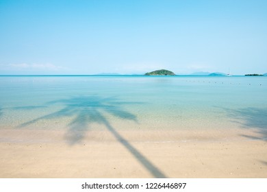 Beautiful shadow of palm tree on the blue sea in summer. Relaxation tropical seascape, yacht, green islands and light blue sky backgrounds. Sunshine day. Koh Mak Island, Trat, Thailand. Vacation time.