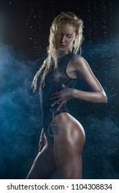 Beautiful shapely athletic big breasted blonde girl with wet oiled body wearing black translucent sexy bodysuit under falling water drops holds handcuffs in her hands on black. Copy space.