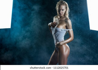 Beautiful shapely athletic big breasted blonde girl with wet oiled body wearing white translucent sexy bodysuit posing sideways in scenic smoke under falling water drops of rain on black. Copy space