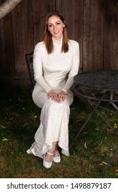 Beautiful shapely brunette in a long white dress