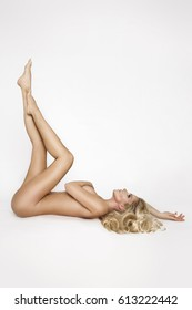 Beautiful, shapely female model with long blond hair, lies naked on a white background and covers the bust