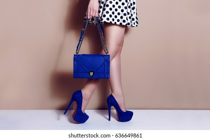 Beautiful shapely legs in high heels shoes. Woman wearing polka dots dress with blue bag