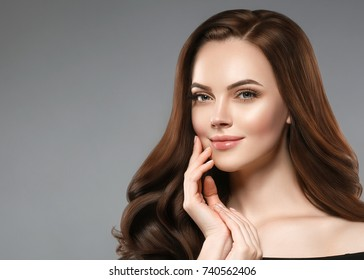 Beautiful shine hair woman with manicure nails hand. Brunette with long hair and healthy skin over gray background.