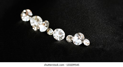 Beautiful shining crystals (diamonds), on black cloth background