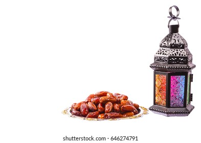 Beautiful a shining Fanus lantern and dried dates on a silver tray isolation on white background. The Muslim feast of the holy month of Ramadan Kareem. Free space for your text.