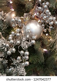 Beautiful shiny silver christmas balls hanging on xmas tree with silver berries and glowing lights.