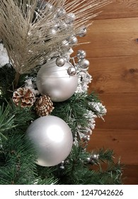 Beautiful shiny silver christmas balls hanging on xmas tree with pine cones and silver.