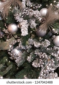 Beautiful shiny silver and glittering christmas balls hanging on snowy xmas tree branches with silver berries and glowing lights.