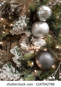 Beautiful shiny silver and glittering christmas balls hanging on snowy xmas tree branches with glowing lights.