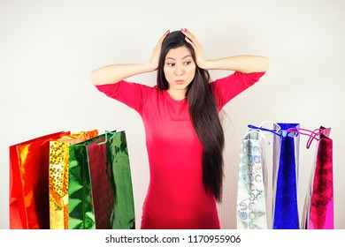 beautiful shocked brunette mad woman shopaholic in dress looks at the shopping bags . concept of seasonal sales and shopaholicism.