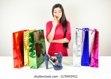 beautiful shocked brunette mad woman shopaholic in dress looks at stylish shoes and clothes on a hanger and shopping bags . concept of seasonal sales , shopaholicism and spending all of money