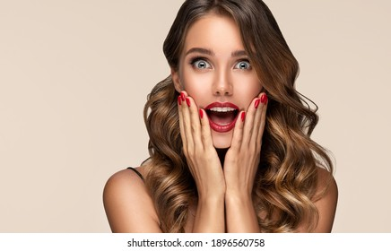 Beautiful shocked and surprised woman screaming .Beauty female with wavy hairstyle. Curly hair girl amazed . Expressive facial expressions . Red nails manicure.Beauty , cosmetic and makeup