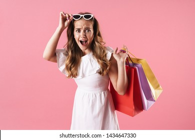 Beautiful shocked young blonde girl wearing summer dress standing isolated over pink background, carrying shopping bags