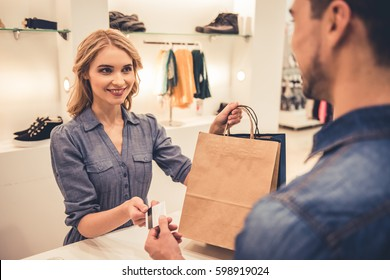 Beautiful shop assistant is smiling while giving purchases and credit card to handsome client