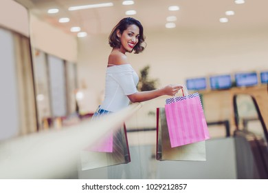 Beautiful shopping woman smiling and holding bags in shopping mall