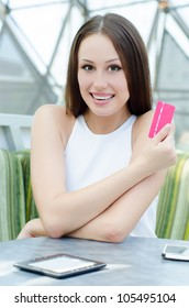 Beautiful shopping woman wearing stylish white dress. holding new credit card