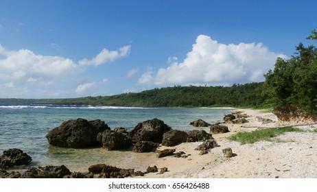 Beautiful shoreline of Wing Beach, Saipan Rocks line up along the white sand beach strip of Wing Beach in Saipan, Northern Mariana Islands.