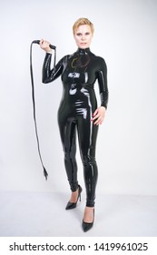 Beautiful short hair strong woman posing as fetish vamp mistress in glamour latex clothes with black leather bdsm whip. Curvy girl standing in sex shop white room alone.