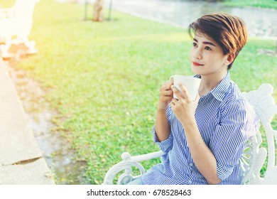 Beautiful short hair woman sitting on a white chair and drinking a favorite beverage in white cup for resting between her outdoor working business in the park.