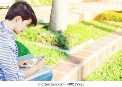 Beautiful short hair woman sitting on the floor and writing a note for outdoor working her business in the park.