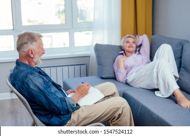 beautiful short haired good-looking woman lying on the couch,old man artist sitting next to her on chair and drawing in day light living room with big window