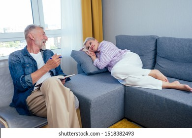 beautiful short haired goog-looking woman lying on the couch,old man artist sitting next to her on chair and drawing in day light living room with big window.