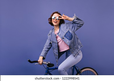 Beautiful short-haired girl in sparkle glasses sitting on bike. Cheerful female model posing on bicycle and expressing happiness.
