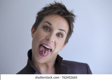 beautiful short-haired woman rolling her tongue in the shape of a three-leaf clover
