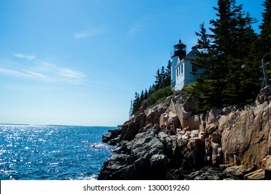 Beautiful shot of Bass Harbor Headlight on Mount Desert Island over the summer. View of the lighthouse, ocean, granite rocks, and the pine trees around it