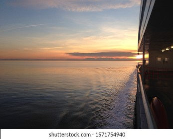 A beautiful shot of a body of water done from a ferry during sunset