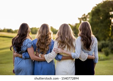A beautiful shot of four female with their arms around each other and a blurred background