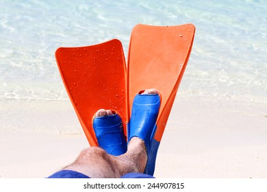 A beautiful shot of a mans feet wearing orange and Blue swimming flippers on a tropical beach