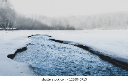 Beautiful shot of misty lake in north with ice on the side. Small foggy lake in winter time with crystal blue flowing watter. Amazing frozen and snow covered lake in Europe