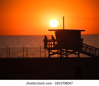 A beautiful shot of people watching the sea from a lifeguard spot during an orange sunset