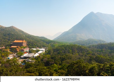 Beautiful shot of the Po Lin Monastery site and Lantau Island's mountains. Luxurious nature surrounding the famous buddhist temple. Sunny peaceful day.