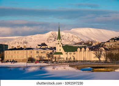 Beautiful shot of Reykjavik downtown with lutheran church in a golden evening light. Capital city of Iceland Reykjavik in winter surrounded with snow covered mountains.