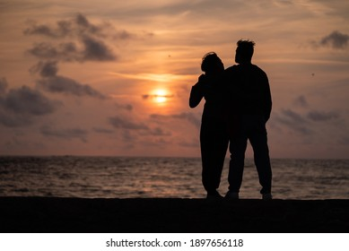 A beautiful shot of the siluette of a loving couple admiring the ocean in Guernsey at sunset