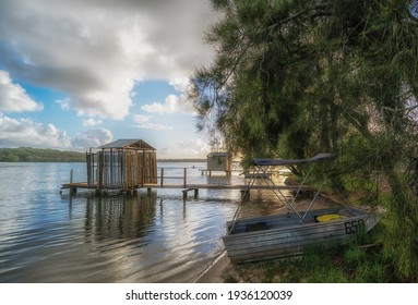A beautiful shot of small rustic boatsheds on background of the cloudy blue sky