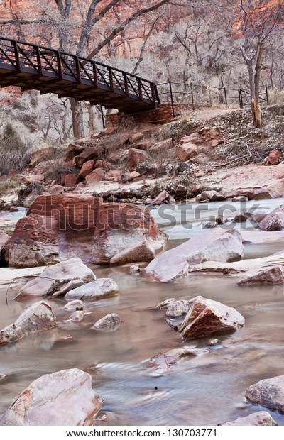 Beautiful shot of the Virgin River with a bridge and red sandstone in Zion's National Park