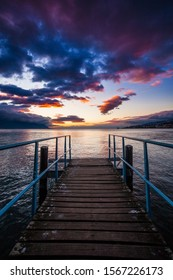A beautiful shot of a wooden dock near the sea with the reflection of the sunset under the cloudy sky