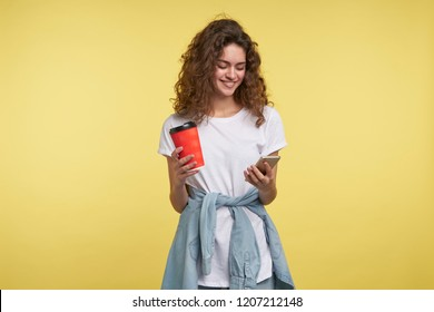 Beautiful shy brunette woman chatting via whatsapp messenger she holding coffee cup, a shot isolated over yellow background