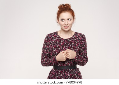 Beautiful shy timid redhead woman, her face being frightened, scared or ashamed. Body language. Studio shot on gray wall