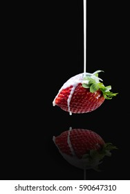 Beautiful side view of milk stream flowing to the delicious ripe strawberry with reflections on dark background