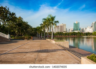 beautiful sidewalk along big lake in lights of sunset in center of bangkok, walking path in one of parks in Bangkok, landscape of park with palms and lake and skyscrapers on background
