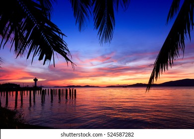 Beautiful Silhouette coconut palm tree and Lighthouse on the tropical beach and sea with sunset time in Ranong, Thailand opposite Kawthaung in Myanmar. caribbean and hawaii. Koh Tao